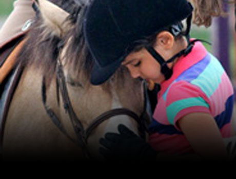 A Stonewood Riding Academy student hugging her horse after a horseback riding lessons in Pickering, Ontario.